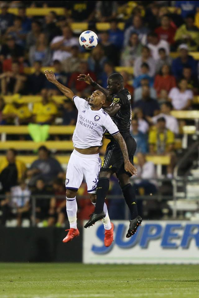 Jul 21, 2018; Columbus, OH, USA; Columbus Crew SC defender Jonathan Mensah in a mid-air challenge in the victory over Orlando City SC at MAPFRE Stadium. Mandatory Credit: Aaron Doster-USA TODAY Sports